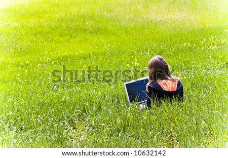 Blonde woman connected to internet in a meadow - stock photo