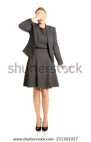 Blonde woman covering her face with both hands - stock photo