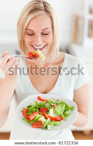 Blonde woman eating salad in the kitchen - stock photo