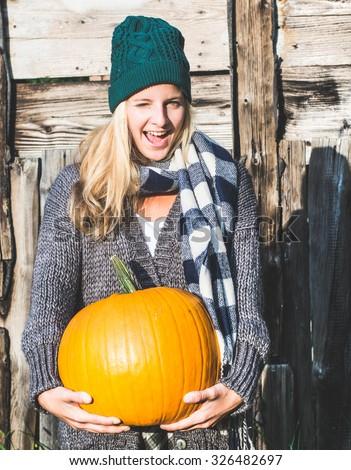 Blonde woman holding halloween pumpkin outdoor - stock photo