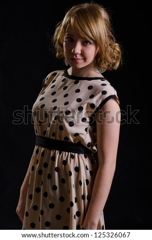 Blonde woman in American 60s style in polka dot dress - stock photo