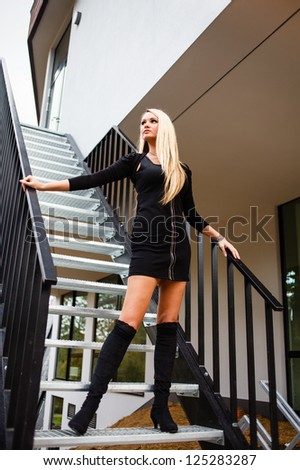 Blonde woman in black short dress on staircase. - stock photo