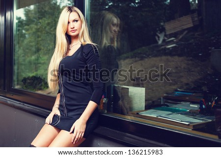 Blonde woman in black short dress sitting on windowsill. - stock photo