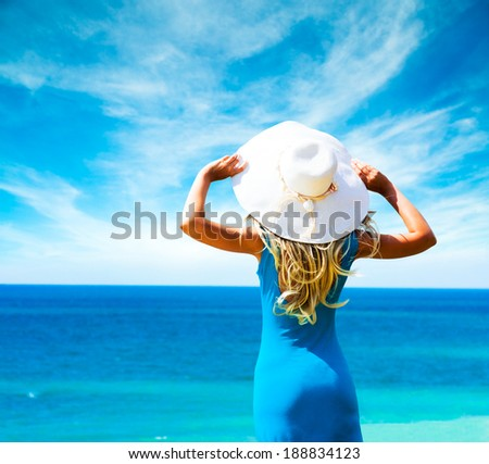 Blonde Woman in Blue Dress Standing at Sea and Holding White Hat. Rear View. Summer Vacation Concept. - stock photo