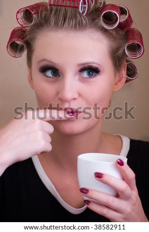 blonde woman in curlers and a cup of coffee in hand - stock photo