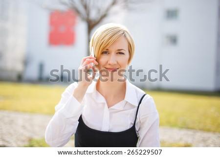 Blonde woman in formal wear calling outdoor, businesswoman - stock photo