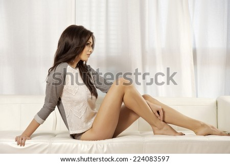 blonde woman in gray sweater on the white sofa - stock photo