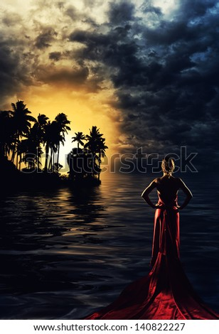 Blonde woman in red dress at sunset in a tropical resort - stock photo