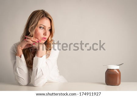 Blonde woman looking at chocolate cream.  - stock photo
