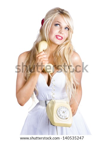 Blonde woman looking up to communication copy space with old-fashion rotary telephone held in hand - stock photo