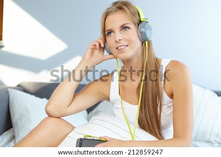 Blonde woman lying on bed while listening music through headphone  - stock photo