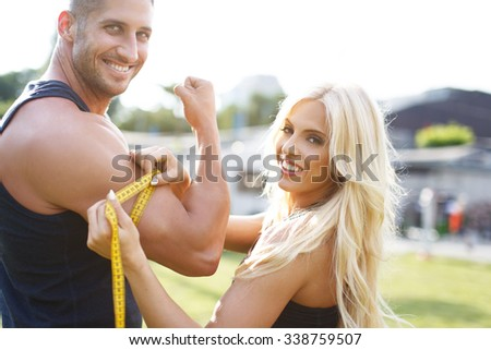 Blonde woman measure mans biceps by yellow measuring tape in nature - stock photo
