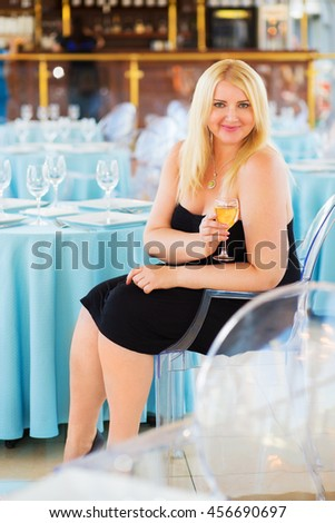Blonde woman sits at table in ship restaurant and holds wine glass - stock photo