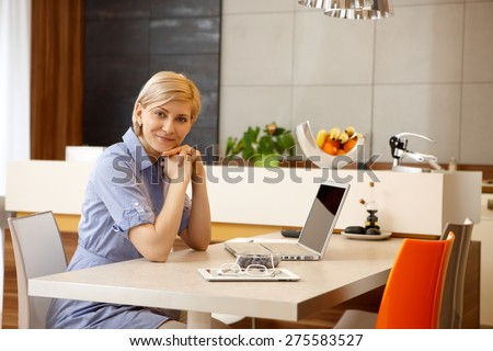 Blonde woman sitting at table at home, using laptop computer, smiling, looking at camera. - stock photo