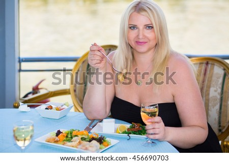 Blonde woman sitting at table in ship restaurant, eating and drinking wine - stock photo