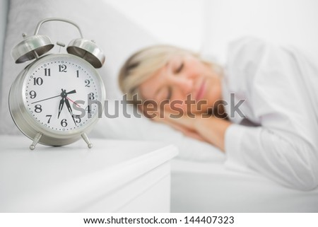 Blonde woman sleeping in bed at home beside alarm clock - stock photo