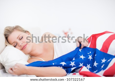 Blonde woman sleeping with a US flag on her bed - stock photo