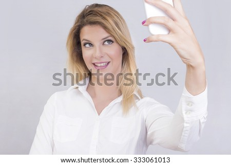 Blonde woman taking a photo of herself with her cell phone - stock photo