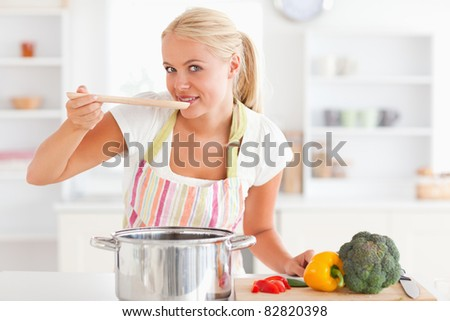 Blonde woman tasting her meal while looking at the camera - stock photo