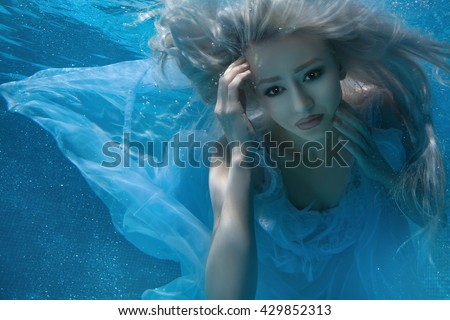 Blonde woman under water, her long hair and a white dress. - stock photo
