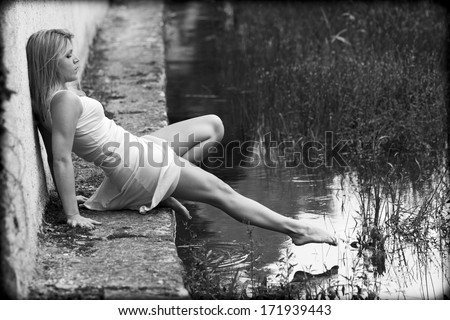 Blonde woman, wearing a white dress, is sitting on the edge of a pond. She is barefoot. She tries to touch the water with her toe.  - stock photo