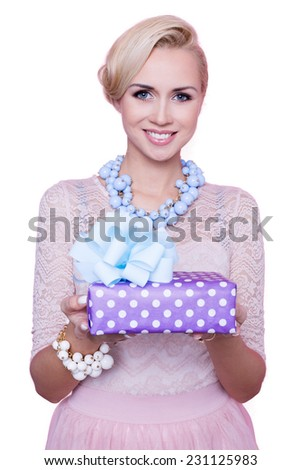 Blonde woman with beautiful smile giving colorful gift box. Christmas. Holiday. Studio portrait isolated over white background   - stock photo