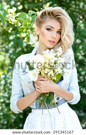 Blonde woman with bouquet in springtime.  - stock photo
