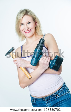 Blonde woman with hammer and screwdriver in her hands - stock photo