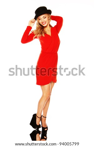 Blonde woman with long slender legs wearing a red dress and black hat on a mirror base. - stock photo