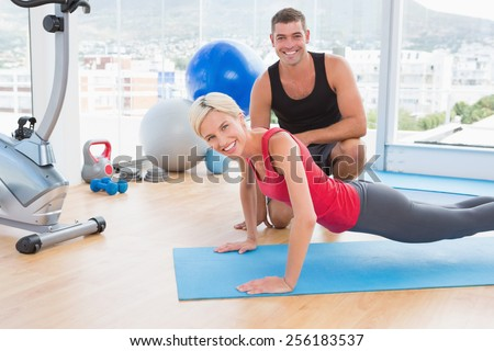 Blonde woman working on exercise mat with her trainer in fitness studio - stock photo