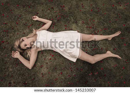 Blonde women wearing white dress laying down with red roses around her - stock photo