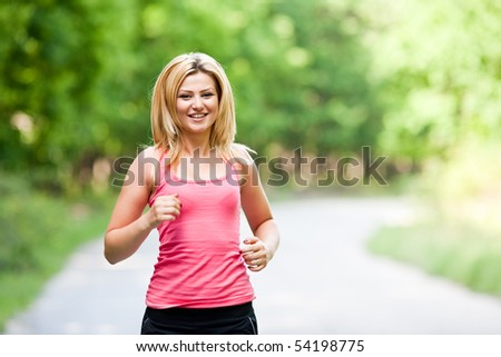 Blonde young lady running through the forest - stock photo