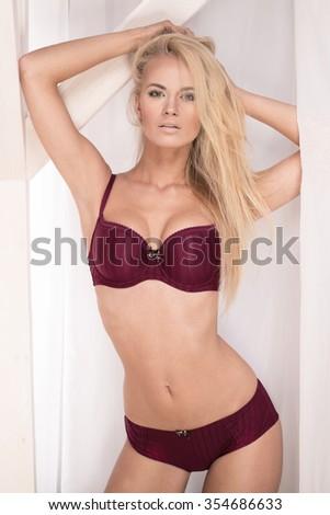 Blonde young sensual woman posing in elegant lingerie, looking at camera. Perfect slim body. Natural makeup. - stock photo