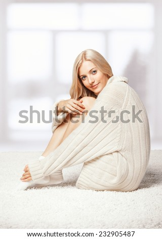 Blonde young woman dressed in long white cashmere sweater sitting on white whole-floor carpet and window  background - stock photo