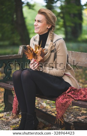 Blonde young woman holding autumn leaves - stock photo