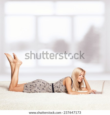 Blonde young woman on white whole-floor carpet browsing laptop  near window - stock photo
