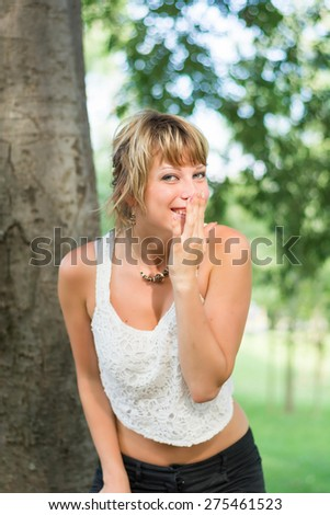 Blonde young woman outdoors laughing and hiding mouth with her hand, with cheeky expression - stock photo