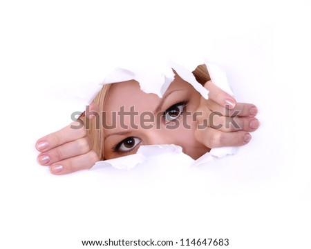 blonde young woman peeping through hole on paper - stock photo