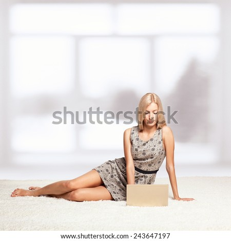 Blonde young woman sitting on white whole-floor carpet browsing laptop  near window - stock photo