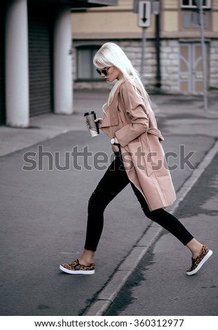 Blonde young woman walking outdoors - stock photo