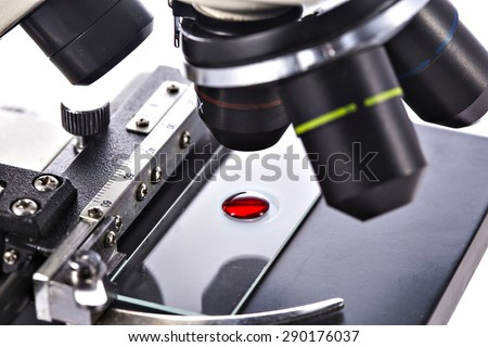 Blood drop sample on test glass plate under microscope lens. Medical laboratory equipment. - stock photo