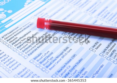 Blood in test tubes and investigation form on the table, close-up - stock photo