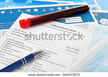 Blood in test tubes, pen and investigation form on the table, close-up - stock photo