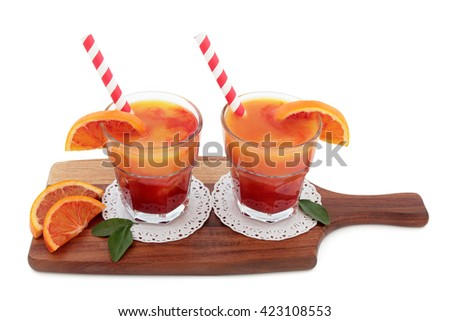 Blood orange fruit juice drink in glasses on doilies with striped straws on a maple wood board over white background. High in vitamins, anthocyanins and antioxidants. - stock photo