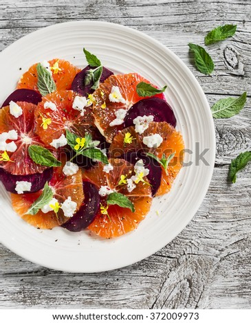 Blood oranges and beet salad with feta, mint and balsamic dressing on rustic white wooden background - stock photo
