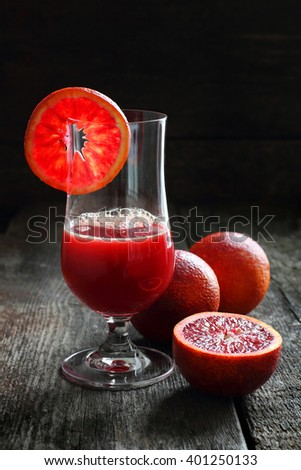 blood oranges and juice of blood oranges on a wooden background, shot with natural light - stock photo