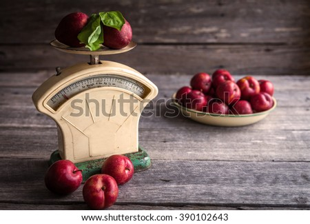 Blood plums on vintage scales against wooden background - stock photo