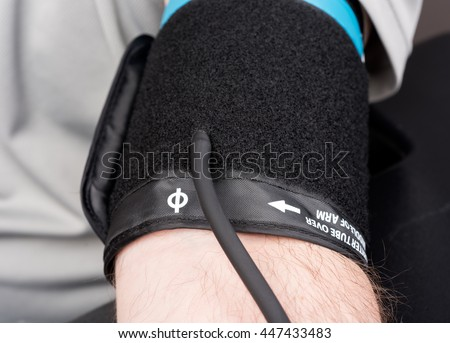 Blood pressure cuff on a man's arm for blood pressure test. - stock photo