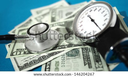 Blood pressure device and stethoscope  with money - high costs of expensive medication concept  - stock photo