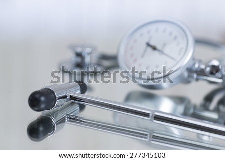 Blood pressure gauge and stethoscope and reflex hammer - stock photo